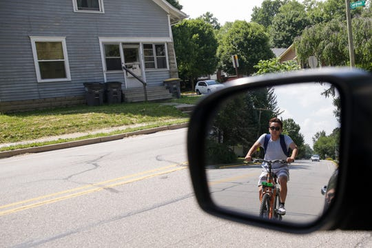A bicyclist is reflected in a side-view mirror, Tuesday, July 2, 2019 in West Lafayette.