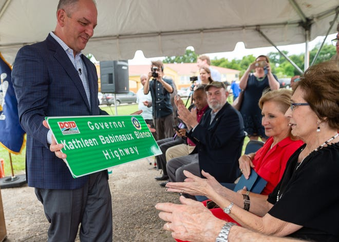 """Louisiana Gov. John Bel Edwards presents former Gov. Kathleen Blanco a sign designating part of U.S. Highway 90 as """"Governor Kathleen Babineaux Blanco Highway"""" at an unveiling ceremony Tuesday, July 2, 2019. The designated portion stretches from its intersection with Interstate 10 in Lafayette to its intersection with Louisiana Highway 308 in Raceland."""