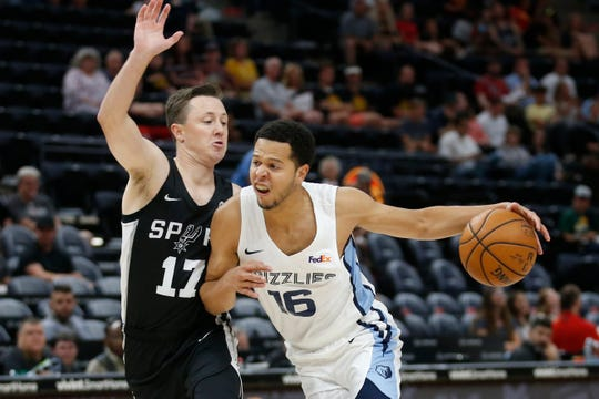 Grizzlies guard Tyler Harvey (16) drives to the basket as Spurs guard Josh Magette (17) defends during the first half of an NBA summer league game July 2 in Salt Lake City.