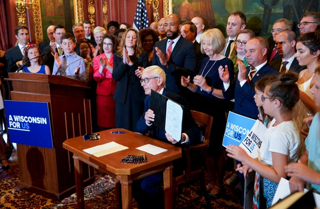 Wisconsin Gov. Tony Evers holds up the budget after signing it at the state Capitol in Madison on Wednesday. Evers made 78 partial vetoes to the state budget passed by the Republican-controlled Legislature before signing it.