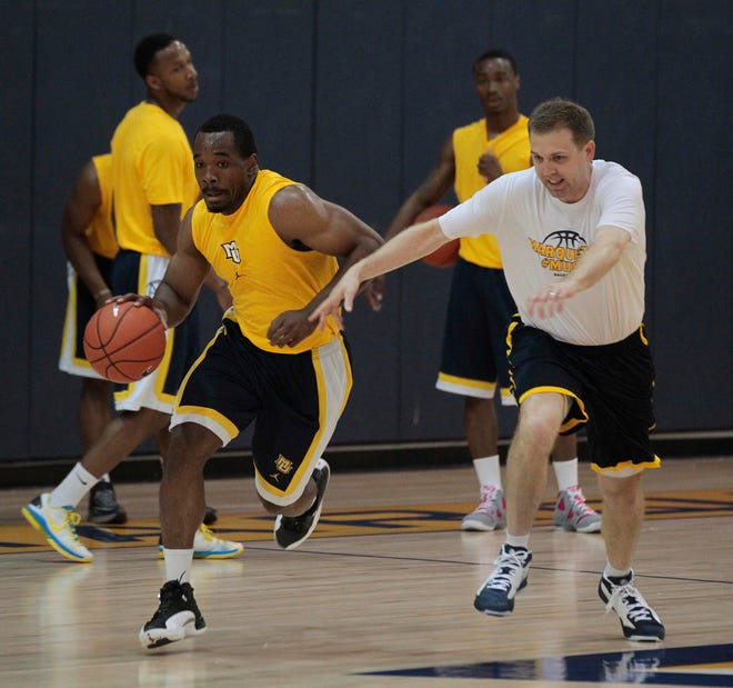 Former Marquette assistant coach Brett Nelson (right) works with ex-Golden Eagles player Derrick Wilson in 2015.