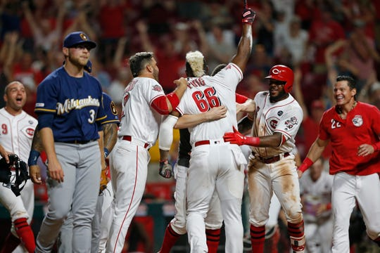 A disgusted Corbin Burnes walks off the field as Yasiel Puig of the Reds celebrates with his teammates after scoring the winning run all the way from first on a single in the 11th inning thanks to a throwing error on Christian Yelich.