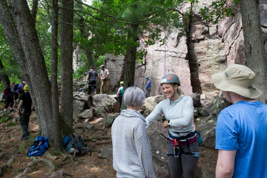 Danielle Williams (from left), Heather Koll and Timothy Hoehnke take a break from rock climbing to talk during a rock climbing trip with First Descents at Devil's Lake on June 22, 2019.
