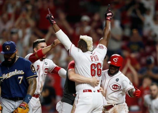 Cincinnati Reds' Yasiel Puig (66) is surrounded by teammates after scoring the winning run against the Milwaukee Brewers during the eleventh inning of a baseball game, Tuesday, July 2, 2019, in Cincinnati. The Reds won 5-4. (AP Photo/Gary Landers)