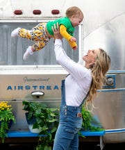 Karla Bradley plays with, her baby Rosalyn, 1, near a 1970 Airstream Caravanner, which she transformed into a whimsical playroom for her kids.