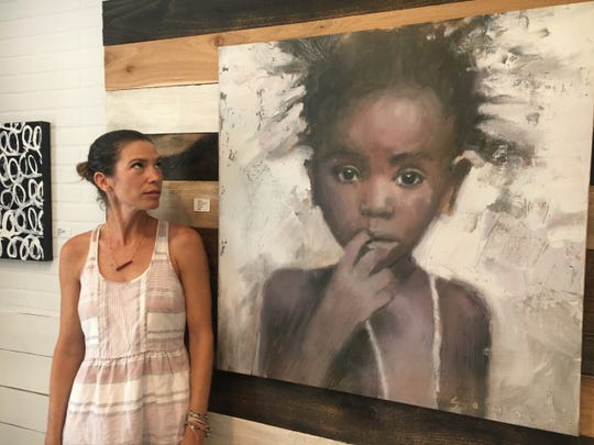 Sam Ornellas glances at a canvas of an orphaned child she painted.