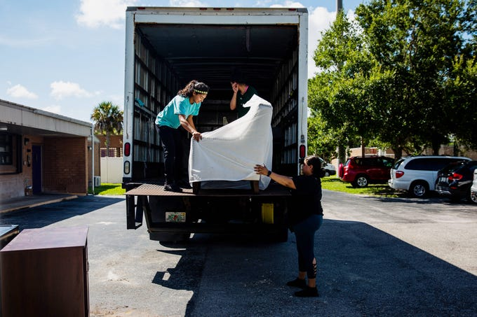 From left, Stephanie Vargas, Valerie Ganza and Samantha Aguilar of the Benison Center deliver furniture to Village Oaks Elementary School in Immokalee on Tuesday July 2, 2019.