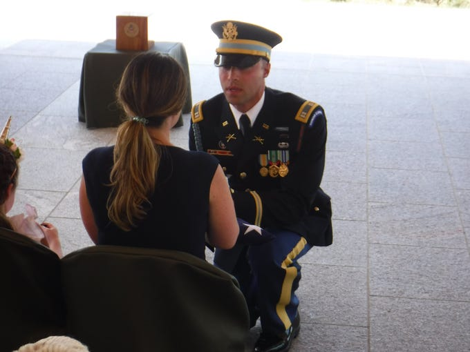 """Tara Barnstead receives the U.S. flag in honor of her father, William J. """"Nick"""" Nicholson at his military service at Arlington National Cemetery on June 28, 2019."""