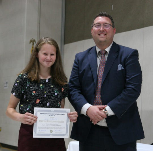 Darya Sulkouskaya, a senior-to-be at Johnstown High School, received a $5,000 scholarship from Newark Rotary Club's Brendan Underwood after Free Enterprise Academy competition.