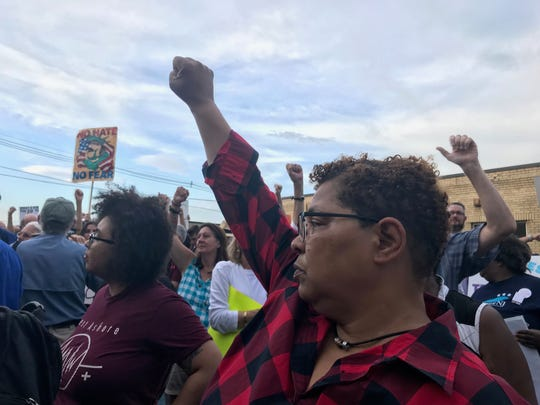 """Demonstrators gather outside the Elizabeth immigration detention center on July 2, 2019 as part of nationwide """"Close the Camps"""" events.  They raise their arm as airplanes fly overhead to show their solidarity with immigration detainees."""