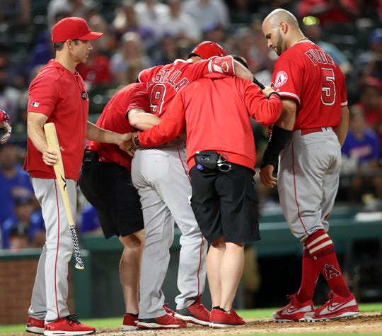 Jul 2, 2019; Arlington, TX, USA; Los Angeles Angels first baseman Albert Pujols (5) and manager Brad Ausmus (12) look on as second baseman Tommy La Stella (9) is helped off the field during the fifth inning against the Texas Rangers at Globe Life Park in Arlington.