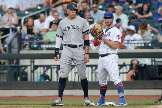 Jul 2, 2019; New York City, NY, USA; New York Yankees right fielder Aaron Judge (99) stands next to New York Mets first baseman Pete Alonso (20) at first base after drawing a walk during the first inning at Citi Field.