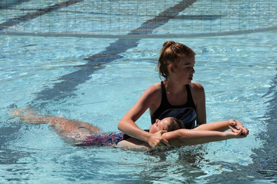 McKenzie Bateman practices rescuing Gracie Baker, Wednesday, July 3, 2019, during lifeguard training at Bisti Bay at Brookside Park.