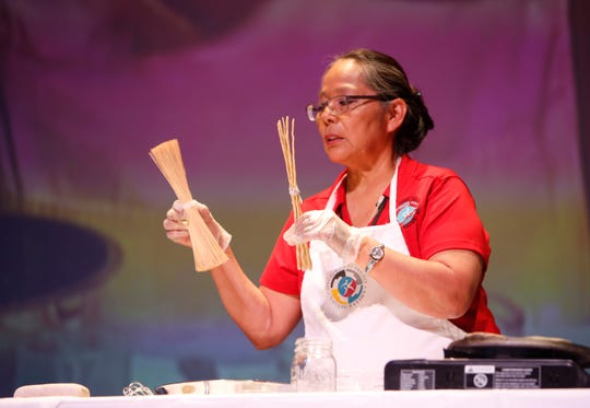 Lena Guerito shows traditional cooking utensils during a food demonstration at the Navajo Nation Special Diabetes Program's Nutrition Summit on July 3 at the Phil L. Thomas Performing Arts Center in Shiprock.