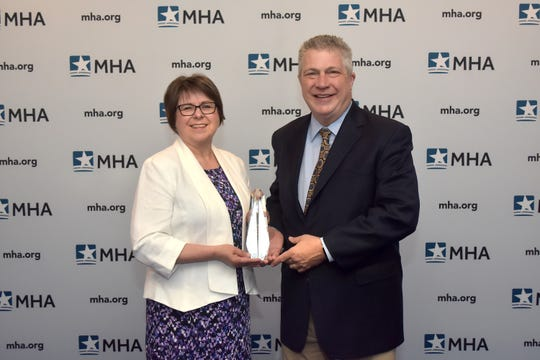 Michaeline Raczka, RD, director of Community Health at St. Mary Mercy Livonia, and David Spivey, president and CEO of St. Mary Mercy Livonia, accept The Michigan Health and Hospital Association's 2019 Ludwig Community Benefit Award on behalf of Healthy Livonia.