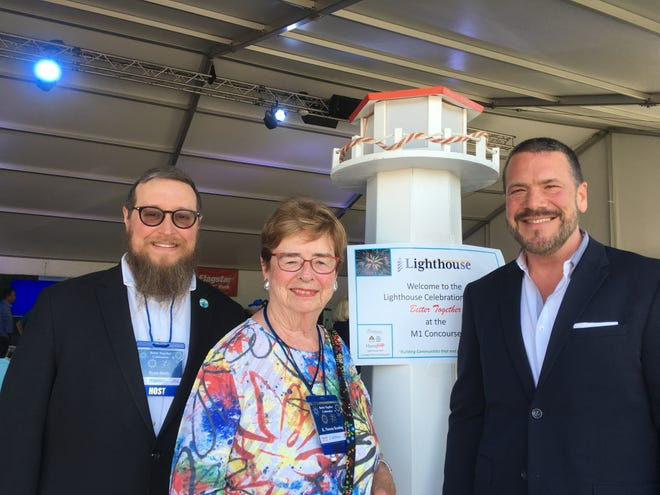 At the M1 Concourse, Ryan Hertz, CEO of Lighthouse, Noreen Keating retired CEO of Lighthouse, and Bill Sullivan of Flagstar Bank meet in the huge tent housing the Better Together Celebration. Lighthouse merged with South Oakland Shelter to serve needy Oakland County residents.
