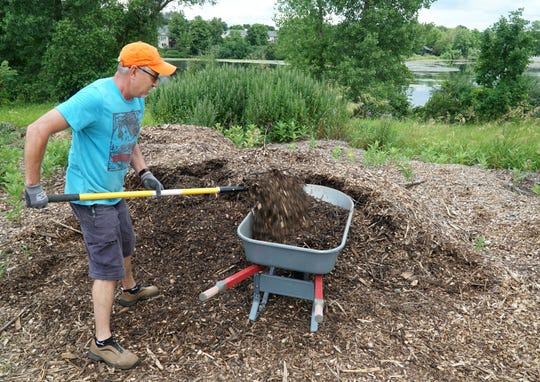 Doug Reed prepares to spread some mulch on the Milford Community Growing Greens garden near Milford and G.M. Road on July 3, 2019. Reed and others involved in the garden were worried that they couldn't use the nearby Huron River's water (seen in the background) to help water their veggies and flowers - due to PFAS contamination. But the village council okay'd the use of the source.