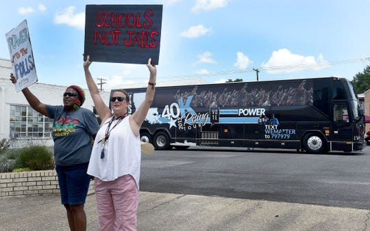 Thelma Henry Taylor, left, and Suzanne DeRoen hold up signs as part of the Black Voters Matter bus tour that stopped in Opelousas Monday afternoon.