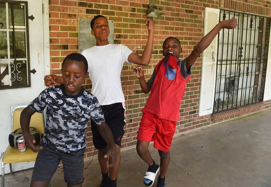 Tre Bailey (left), Bryant Cain and Braylon Cain demonstrate their hip-hop moves Saturday afternoon at the Washington Recreation Center. The youngsters were there to watch the production of a video being made by former Washington resident Vernon Wiggins.