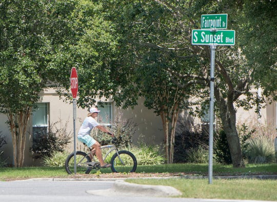 A bicyclist makes his way down South Sunset Boulevard off Fairpoint Drive in Gulf Breeze on Wednesday.