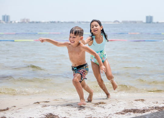 Lyla Peña, 6, chases her brother A.J. Peña Jr., 4, as they play in the water at Shoreline Park in Gulf Breeze on Wednesday.
