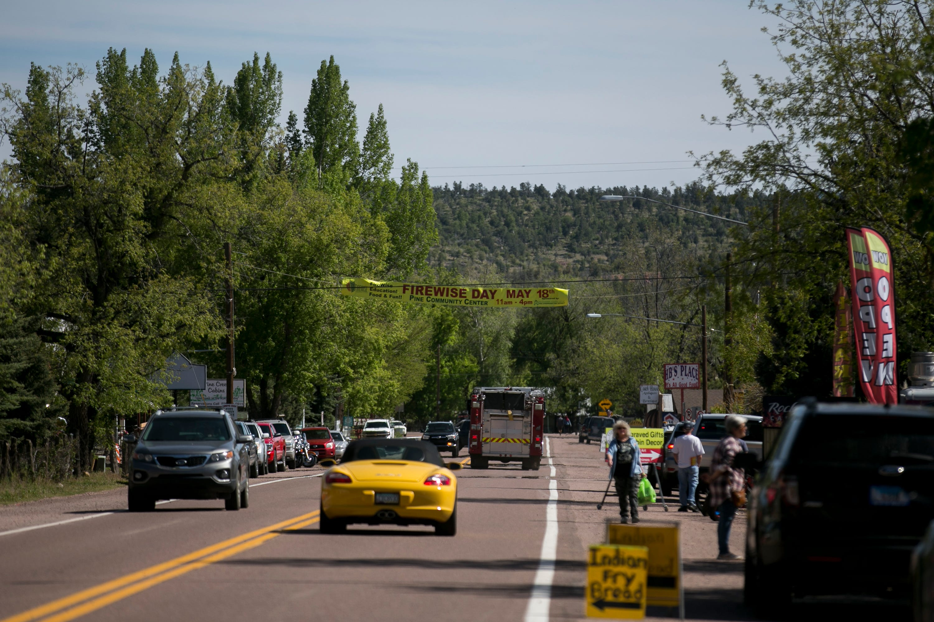 """A banner for """"Firewise Day"""" hangs over the main business strip in Pine, Arizona. The annual event educates locals and visitors on keeping the area safe from fires."""