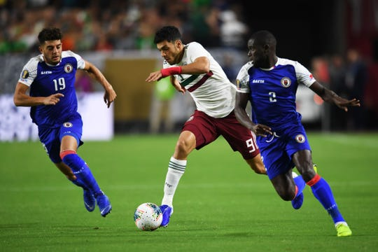 Raul Jimenez elude a dos defensivos de Haiti.