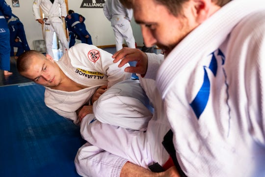Thaddeus McCormick II, 18, left, practices with Paul Elezaj, owner of the Port Huron Brazilian Jiu-Jitsu Academy, during a class Thursday, June 27, 2019.
