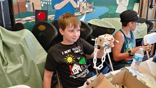 "Jason Dale of Anderson holds up the ""robot"" sculpture he made during the Shasta County Arts Council's art day camp."