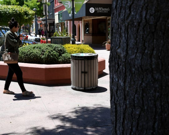 A person walks past a trash can in Old Town Salinas. July 3, 2019.