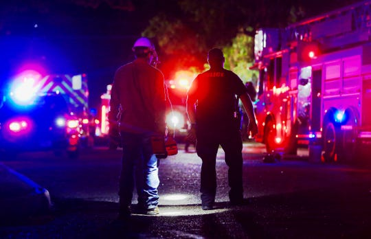 Utility workers and a San Angelo police officer approach the scene of a fire near the intersection of West Avenue K and Austin Street Tuesday night.
