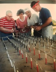 From left: San Angelo Symphony Chorale members Tim Nicholson, Doris Parker, Bob Zentner and Sonny Cleere help assemble an American flag made from fireworks for the July 3 Pops Concert at the RiverStage in this 1990 file photo.