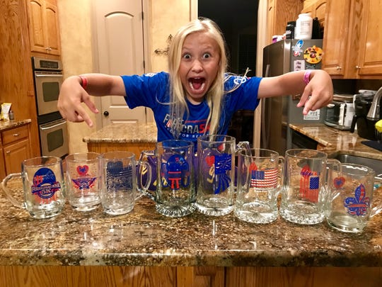 Tilley Armstrong, 8, who hopes to win a collectible mug in the 2019 Sportspectrum Firecracker 5K, points to some of the mugs won by her mother, Shelley.