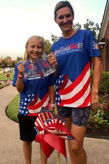 Tilkley and Shelley Armstrong display their Sportspectrum Firecracker 5K mugs and 2019 shirts in front of their home.