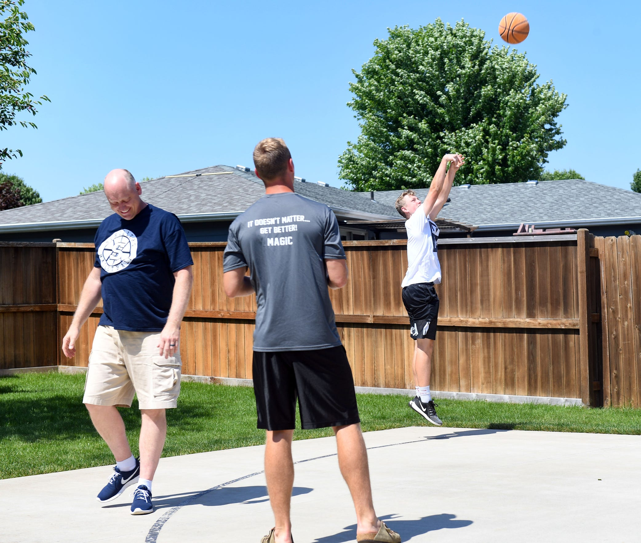 Joe Uttecht shoots a basketball during a game with his father, Dale, and older brother, Logan, on Thursday, June 27, at their home in Sioux Falls.
