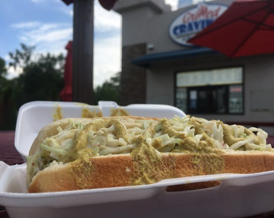 A Zesty Slaw Dog, topped with coleslaw and a spicy brown mustard, is pictured at Grilled Cravings Wednesday, July 3, 2019 in St. Joseph.