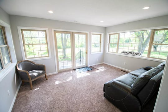 The main floor offers a sunroom for lounging and taking in the property's wooded and private surroundings.