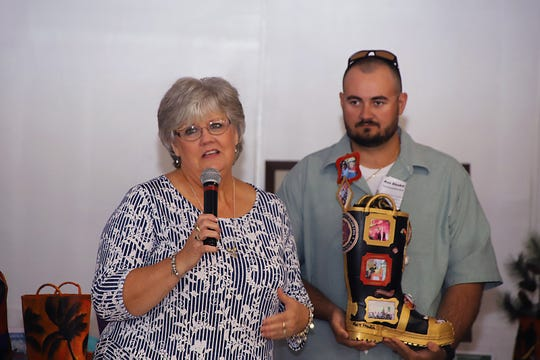 """Debbie and Ethan Brooks accept a boot in honor of  St. Lucie County Fire District Engineer and Hazmat Team member Gary Brooks at the """"Margaritaville"""" themed Lil Feet fundraiser in Fort Pierce."""
