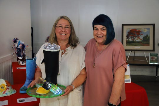 """Christine Chapdelaine and artist Debi Crous with the LandShark boot at the """"Margaritaville"""" themed Lil Feet fundraiser in Fort Pierce."""