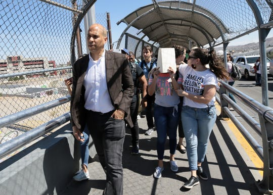 Democratic presidential candidate and U.S. Sen. Cory Booker walks Central American asylum seekers over the international bridge Wednesday, July 3, 2019. They hid their faces behind manila folders.