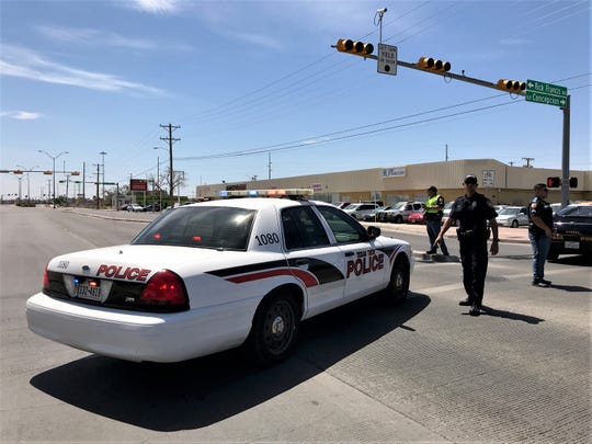 Texas Tech and El Paso police block a street Wednesday as the SWAT team deals with a man with a gun at the Texas Health and Human Services building.