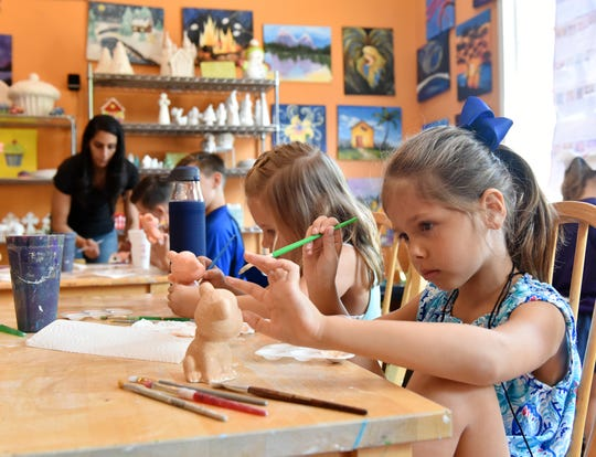 Children work on painting ceramic tigers at Glazed in Clemson.