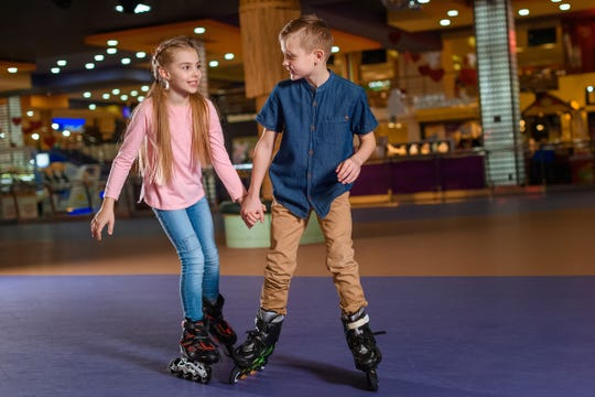 Kids holding hands while skating together on roller rink.