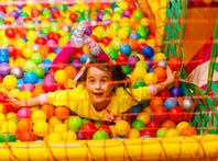 A happy, laughing girl playing with toys and colorful balls in a ball pit.