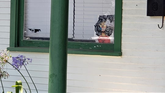 A bullet hole is visible in a front window at the Port Hueneme home where a girl and her mother were injured by gunfire.