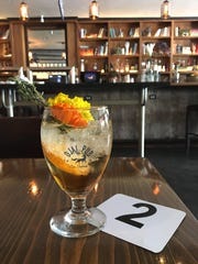 Patrons order food and drink at the bar during weekend brunch service at Ojai Pub. Beverages include cocktails like the Superbloom Spritz, garnished with edible flowers.