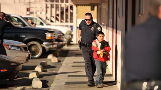 Visalia Police Officer Renny Collins escorts a 7-year-old away from room 143 at the Marco Polo Inn in this 2011 file photo.