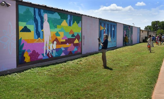 "The fourth of four murals commissioned for the east side of Wichita Falls was unveiled Tuesday morning. The artwork is titled, ""In Motion"", and is painted on the Beacon Lighthouse for the Blind."
