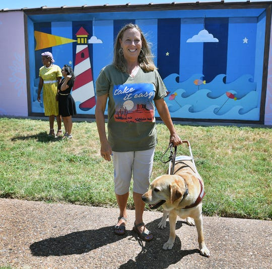 Lisa San Miguel, a visually impaired employee of Beacon Lighthouse for the Blind, and her service dog, Nordic, are pictured in front of a new mural painted by Brea'n Thompson.