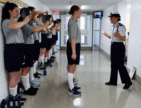 In this July 1, 2019 file photo, female swabs learn the positions of attention and parade rest while their male classmates get haircuts during the first day of a seven-week orientation for the Class of 2023 at the U.S. Coast Guard Academy in New London, Conn.